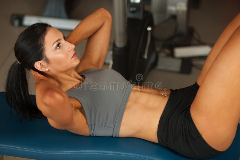 Beautiful young fit woman workout abdominal muscles abs in fitness gym stock image