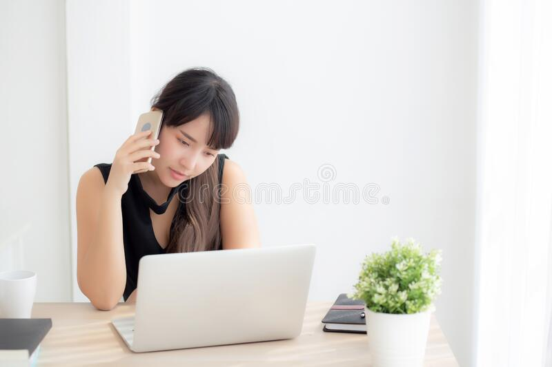 Beautiful young freelance asian woman smiling working on laptop computer and talking mobile smart phone at desk stock photos