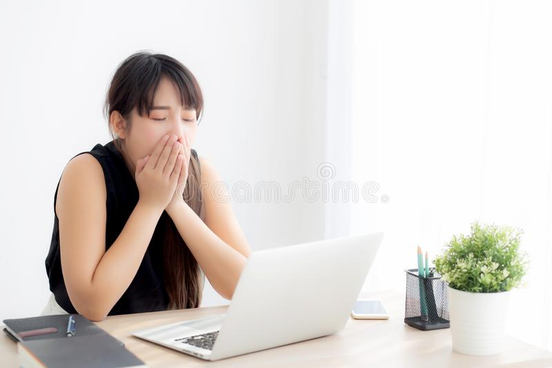 Beautiful young freelance asian woman working bored and tired on laptop computer at the office royalty free stock image