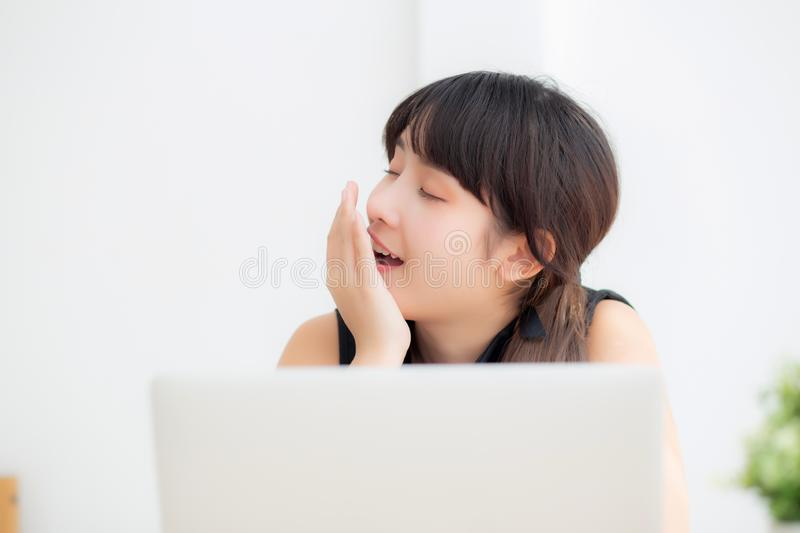 Beautiful young freelance asian woman working bored and tired on laptop computer at the office stock photography