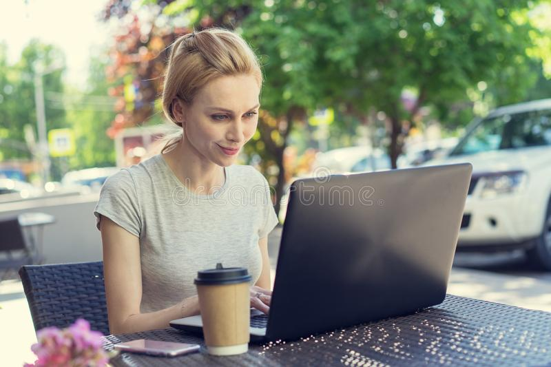 Beautiful young freelancer caucasian woman using laptop computer sitting at cafe. Happy smiling blonde girl working online or stud stock images