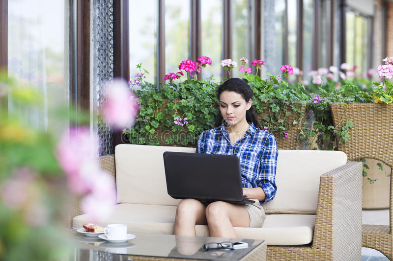Beautiful young freelancer woman using laptop computer sitting a royalty free stock photo
