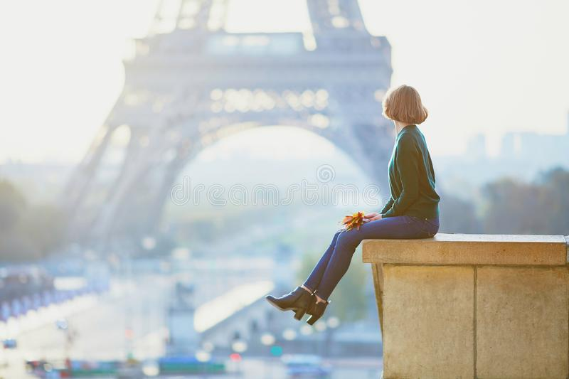 Beautiful young French woman near the Eiffel tower in Paris stock photography