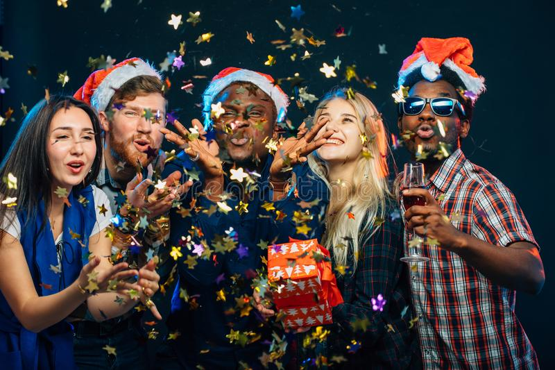 Friends at New Year`s party, wearing santa hats, dancing and blowing confetti royalty free stock image