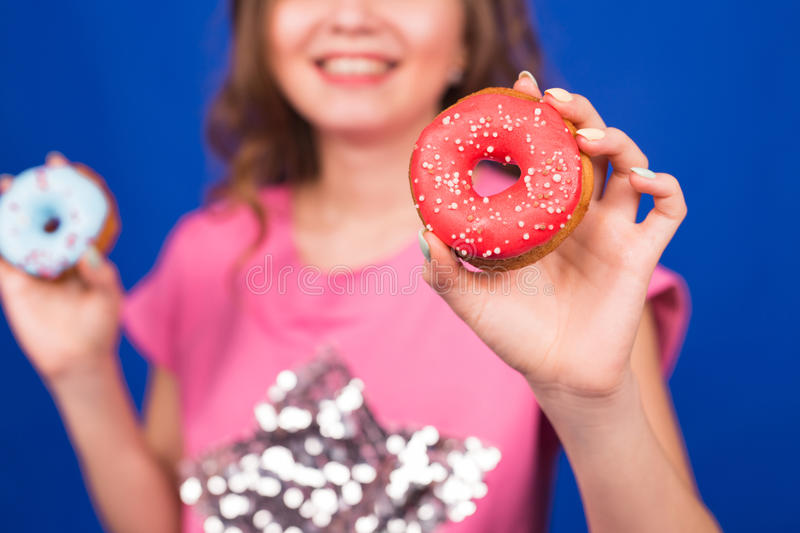 Beautiful young funny girl with donuts on blue background. Unhealthy diet, junk food, party and celebration concept royalty free stock photo