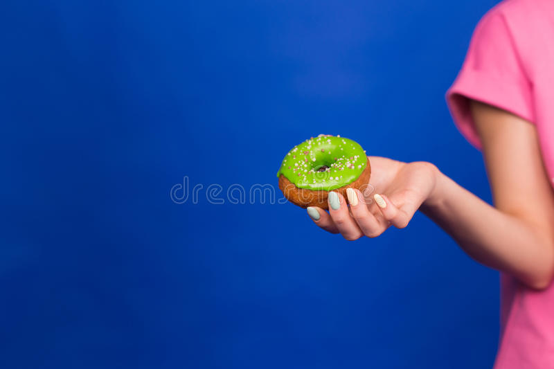 Beautiful young funny girl with donuts on blue background. Unhealthy diet, junk food, party and celebration concept royalty free stock photography