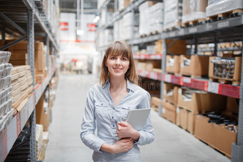 Beautiful young furniture store worker stock taking stock image