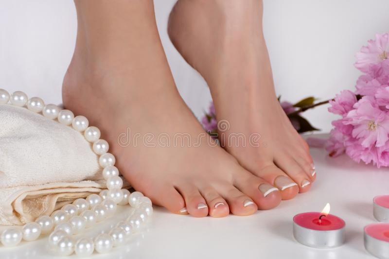 Girl bare feet with french pedicure on white towel and decoration candle, pearls and pink flower. Feet fetish concept. Beautiful young gently woman bare feet stock image