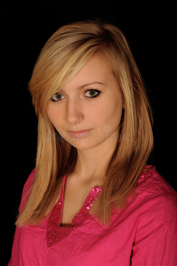 Beautiful Young Girl. A portrait of a beautiful teenage girl in pink, on black studio background stock photos