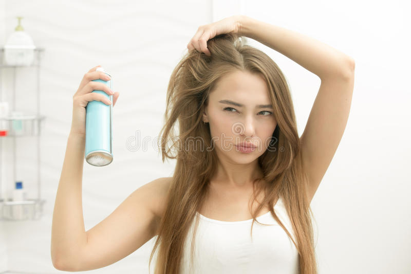 Beautiful young girl applying hair spray on her hair. Choosing a new hairstyle, looking seriously at the mirror, home bathroom interior. Beauty concept photo royalty free stock images
