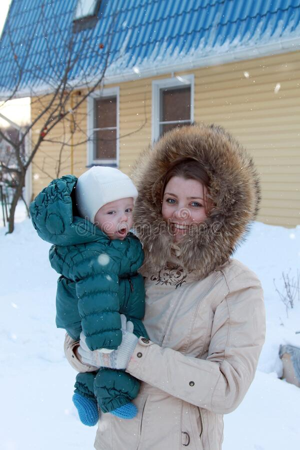 Beautiful young girl with baby boy at sunny winter day. Mother with cute son in backyard. Little boy in green overalls stock image
