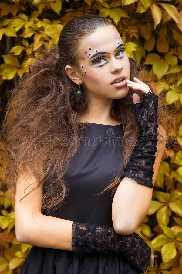 Beautiful young girl on the background of the leaves in autumn day on the street with fantasy makeup in a black dress royalty free stock images