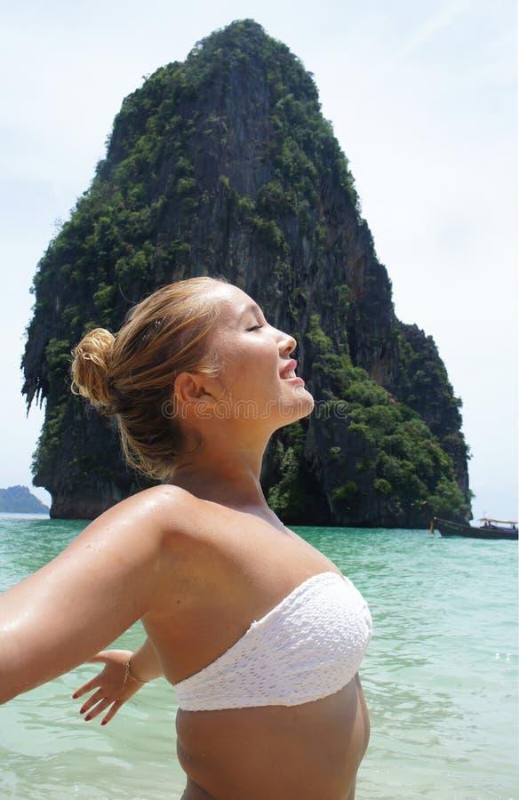 Beautiful young girl on the beach. Beautiful blond girl in white bikini enjoying sunny day on the beach royalty free stock photo