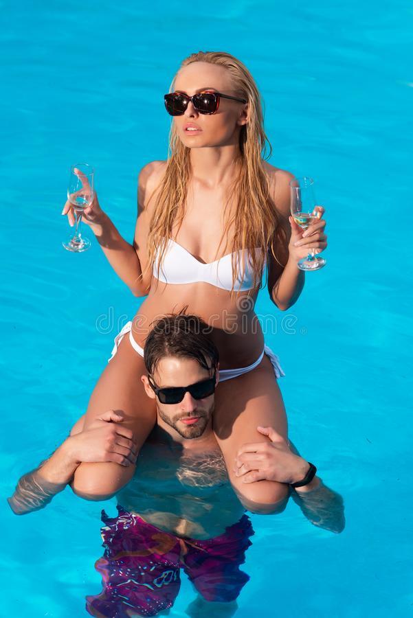 Beautiful young girl on the beach. Sexy couple with champagne wine in swimming pool. Travel. Beautiful young couple in stock photo