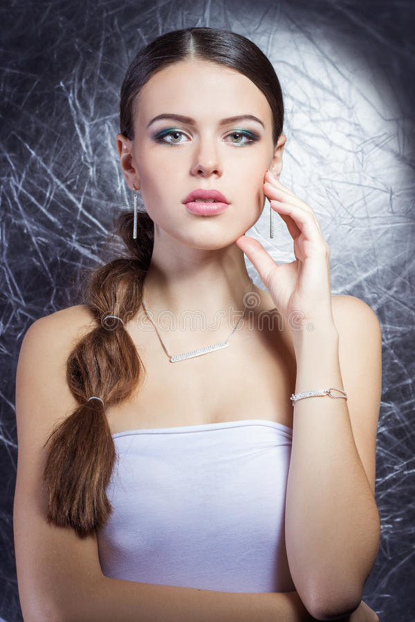 Beautiful young girl with beautiful stylish expensive jewelry, necklace, earrings, bracelet, ring, filming in the Studio stock image