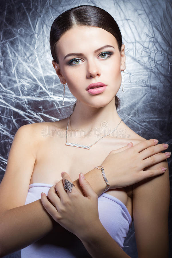 Beautiful young girl with beautiful stylish expensive jewelry, necklace, earrings, bracelet, ring, filming in the Studio royalty free stock photography