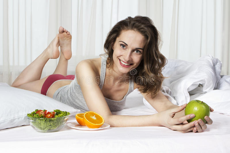 Beautiful young girl in bed eating apple. Beautiful healthy young girl in bed eating apple, orange and salad royalty free stock photography
