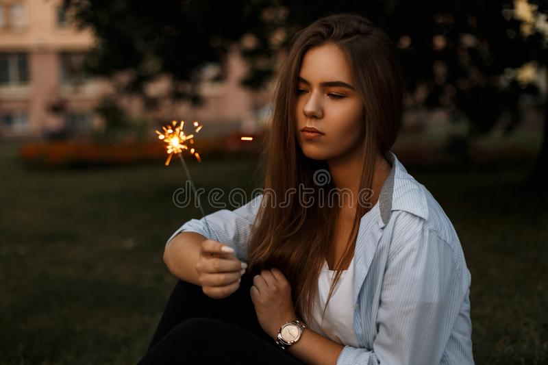 Beautiful young girl with Bengal fire sparkler on the street. stock photography
