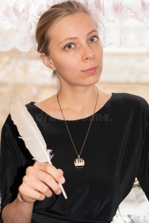 Young girl in black dress is holding white goose feather in her hand and looking at camera. Beautiful young girl in black dress is holding white goose feather stock photography
