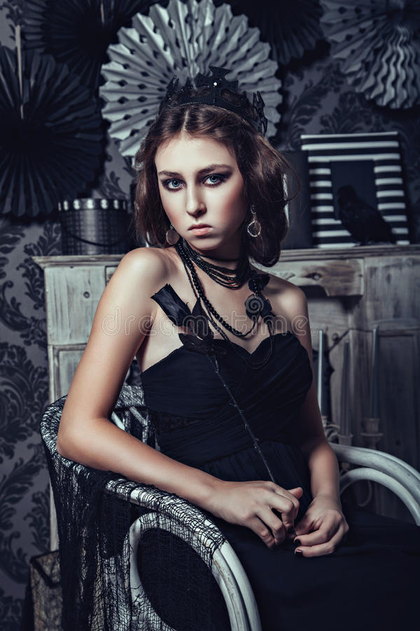 Beautiful young girl in black gothic dress with rose. Beautiful young woman in black gothic dress with rose royalty free stock photo