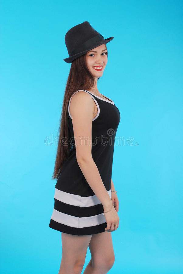 Beautiful young girl in black hat on his head royalty free stock photography