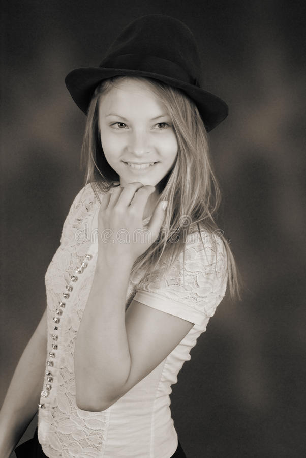 Beautiful young girl in black hat on his head. Black and white vintage effect royalty free stock photo