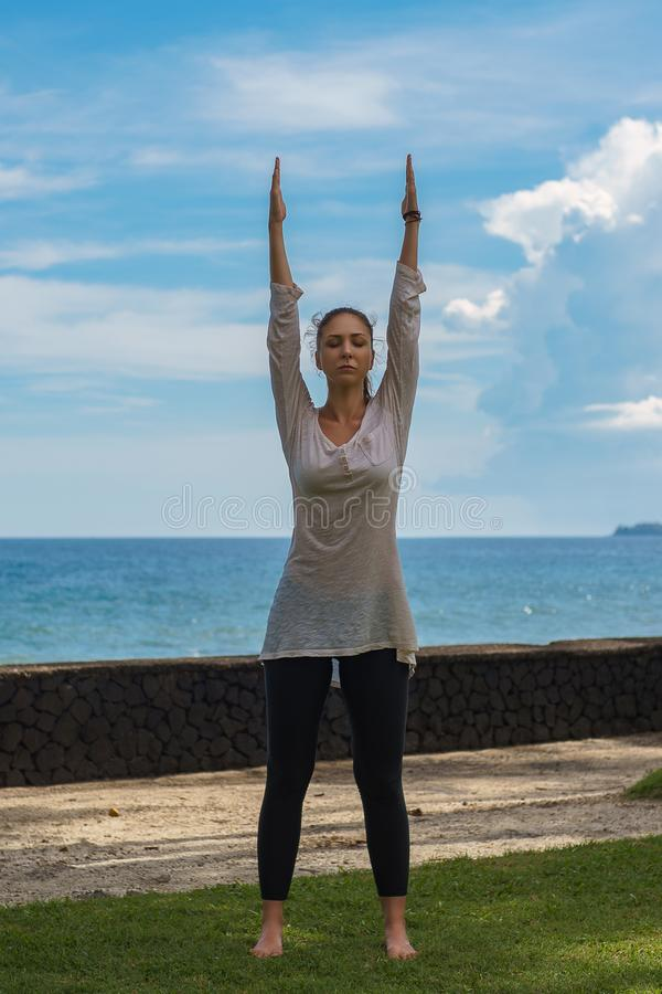 Beautiful young girl in leggings and tunic makes yoga practice, meditation, standing asana on the ocean beach Bali Indonesia. Beautiful young girl in black royalty free stock photos
