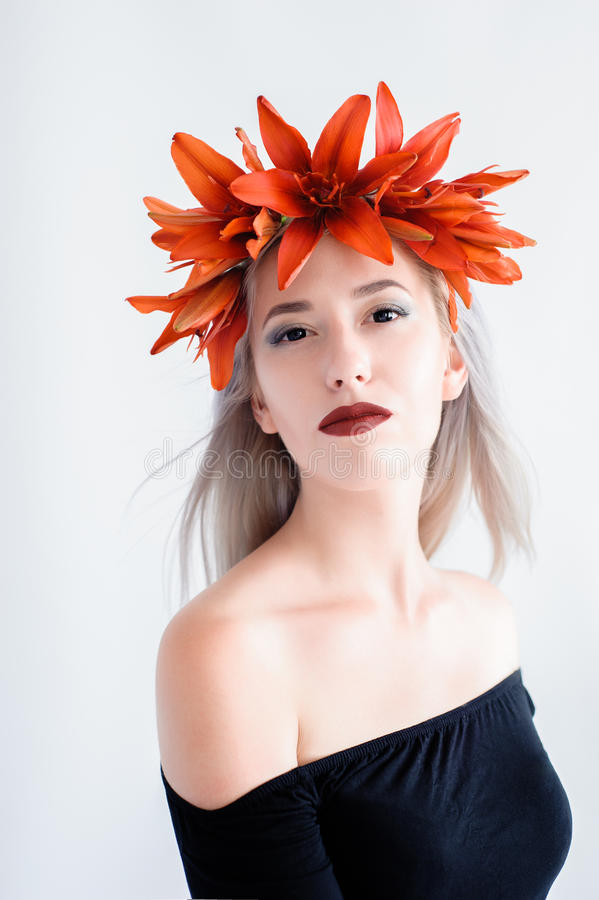 Beautiful young girl in a black lenses with lilies royalty free stock photos
