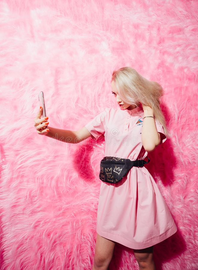 Beautiful young girl blogger dressed in fashion pink dress make a selfie on the background of pink fur wall in the show royalty free stock photography