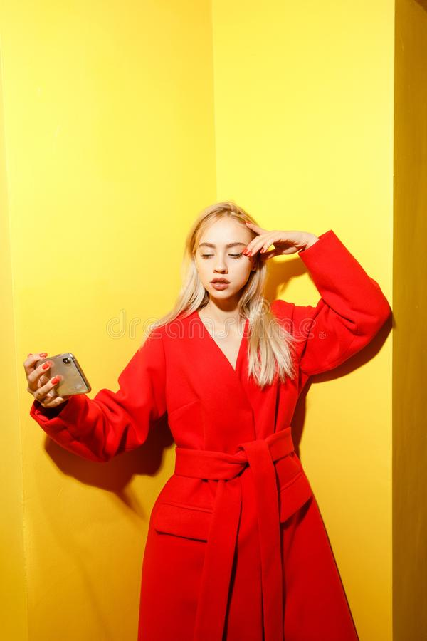 Beautiful young girl blogger dressed in stylish red coat takes a selfie on her smartphone on the background of yellow royalty free stock images