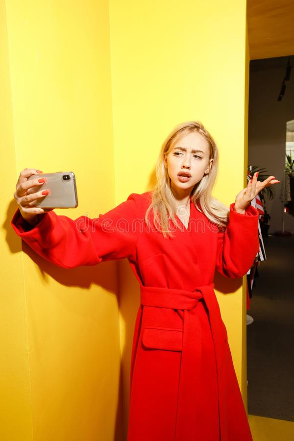 Beautiful young girl blogger dressed in stylish red coat takes a selfie on her smartphone on the background of yellow royalty free stock photo