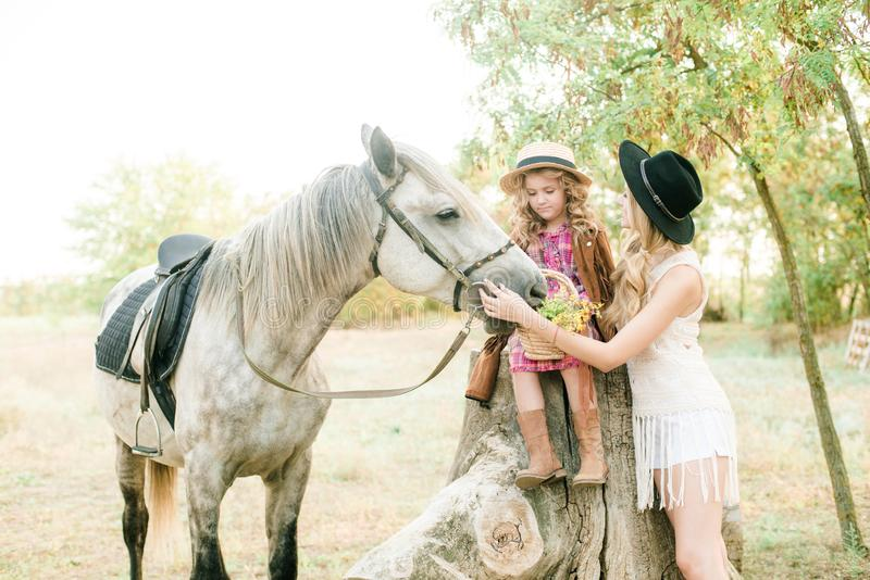 Beautiful young girl with blond hair in a suede jacket with fringe with little sister in a straw hat and checkered vintage dress. With a horse in the royalty free stock photos