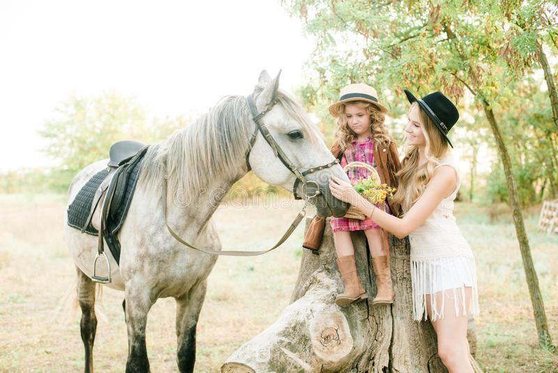 Beautiful young girl with blond hair in a suede jacket with fringe with little sister in a straw hat and checkered vintage dress. With a horse in the stock photo