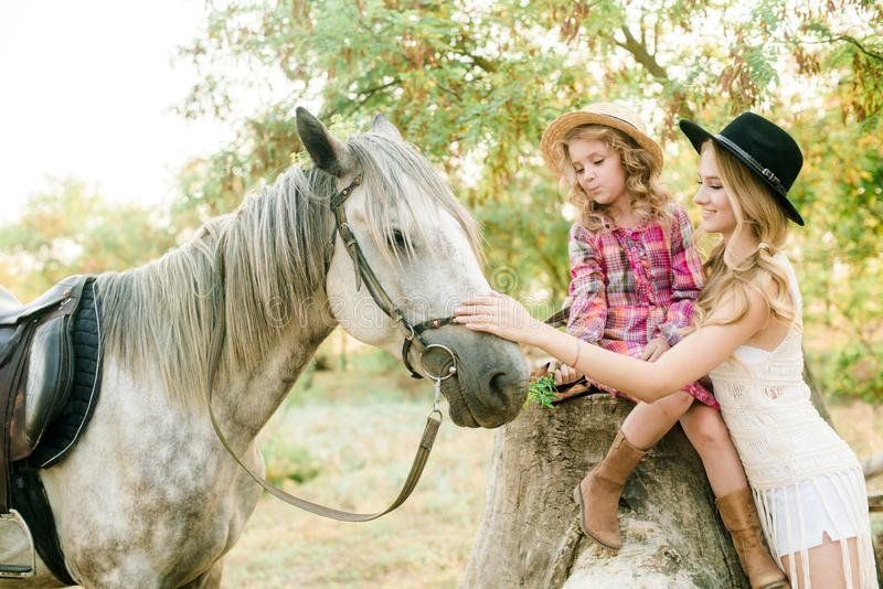 Beautiful young girl with blond hair in a suede jacket with fringe with little sister in a straw hat and checkered vintage dress. With a horse in the royalty free stock images