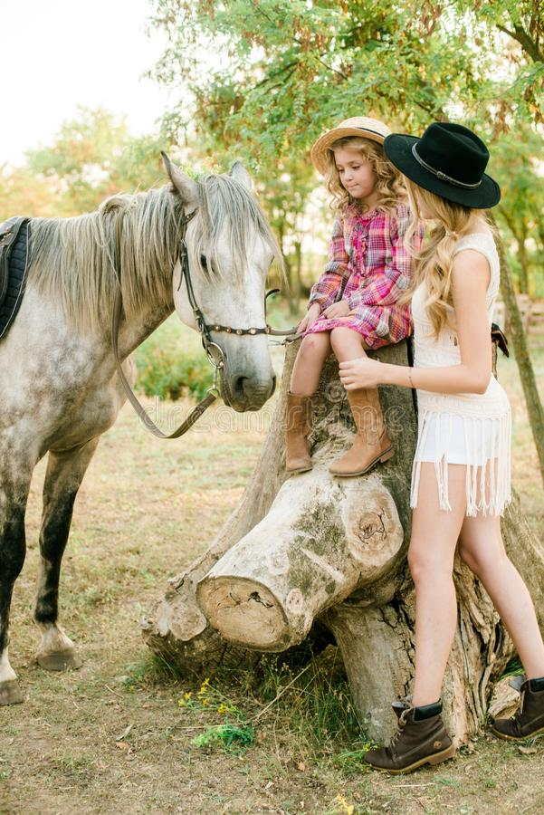 Beautiful young girl with blond hair in a suede jacket with fringe with little sister in a straw hat and checkered vintage dress. With a horse in the royalty free stock image