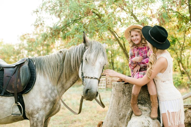 Beautiful young girl with blond hair in a suede jacket with fringe with little sister in a straw hat and checkered vintage dress. With a horse in the stock photos