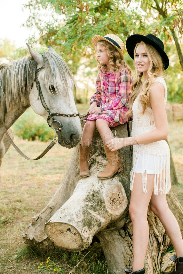 Beautiful young girl with blond hair in a suede jacket with fringe with little sister in a straw hat and checkered vintage dress. With a horse in the royalty free stock photo