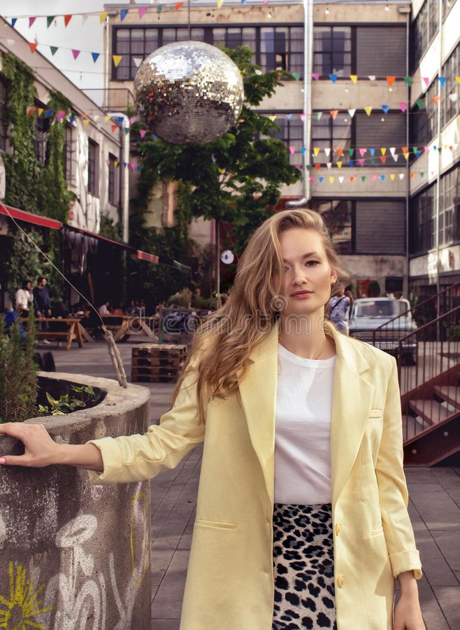 A beautiful young girl blonde in a yellow jacket stands against the background of the city of Tbilisi. Georgia. royalty free stock photos