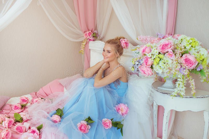 Beautiful young girl at blue dress sits on a bed in a decorated bedroom royalty free stock photo