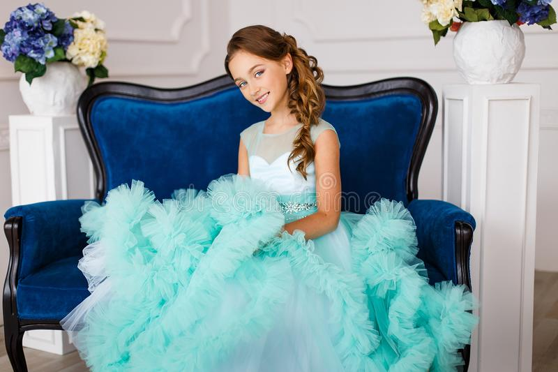 A beautiful young girl with blue eyes, in a lush turquoise dress sitting on a luxury blue couch in a studio royalty free stock photography