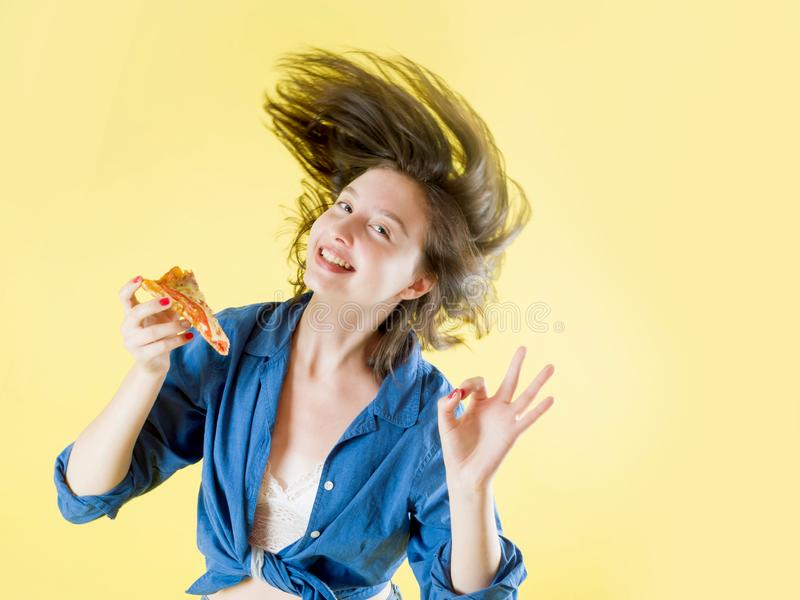 Girl with a piece of pizza in her hands with flying hair on a yellow background. Beautiful young girl in a blue shirt holds in his hand a piece of pizza on a stock photos