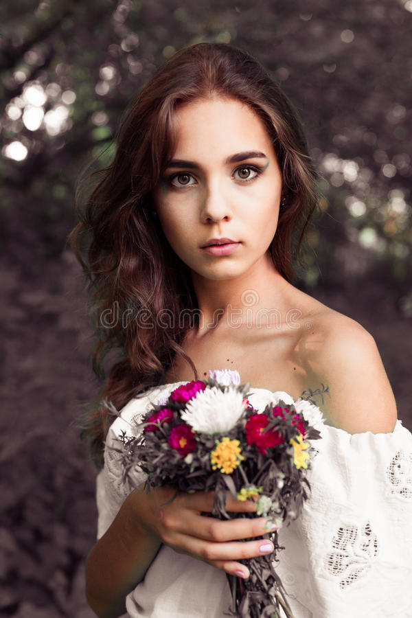 Beautiful young girl with a bouquet of flowers. Beautiful young woman in nice blue dress posing on colorful wall of flowers. Fashi royalty free stock photos