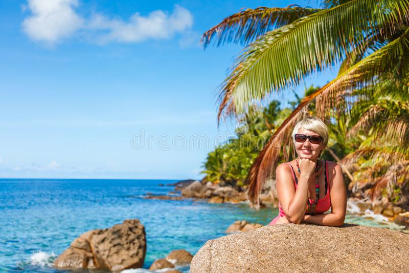 Beautiful young girl in In bright clothes posing under a palm tree on a tropical beach royalty free stock image