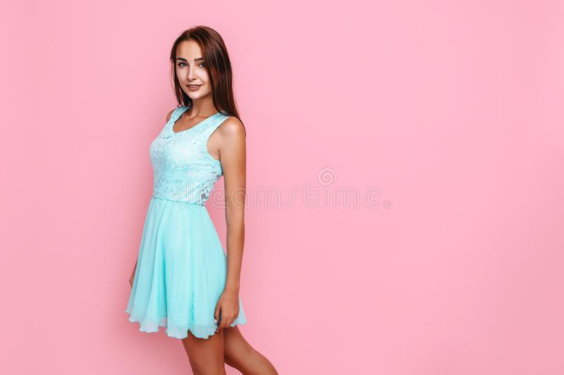Young girl, in a bright dress, smiling and posing on a pink background. Beautiful young girl, in a bright dress, smiling and posing on a pink background royalty free stock images