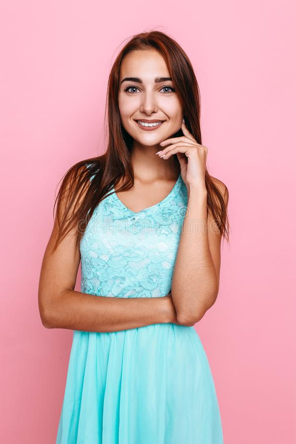 Young girl, in a bright dress, smiling and posing on a pink background. Beautiful young girl, in a bright dress, smiling and posing on a pink background royalty free stock photography