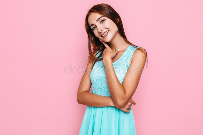 Young girl, in a bright dress, smiling and posing on a pink background. Beautiful young girl, in a bright dress, smiling and posing on a pink background stock photography