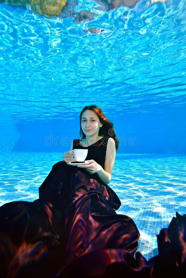 A beautiful young girl in a Burgundy dress sits and poses underwater at the bottom of the pool, holds a white Cup in her hand royalty free stock photography