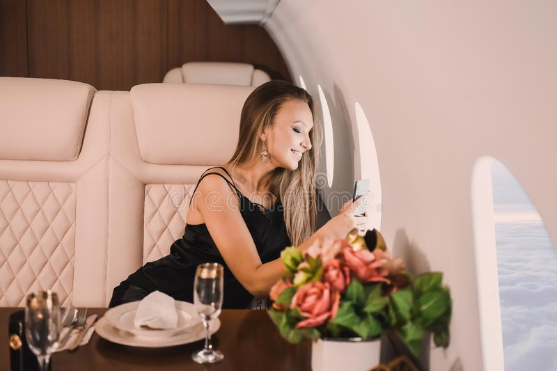 Young girl in the cabin of a business class airplane with a phone in her hands comfortable luxury travel stock photos