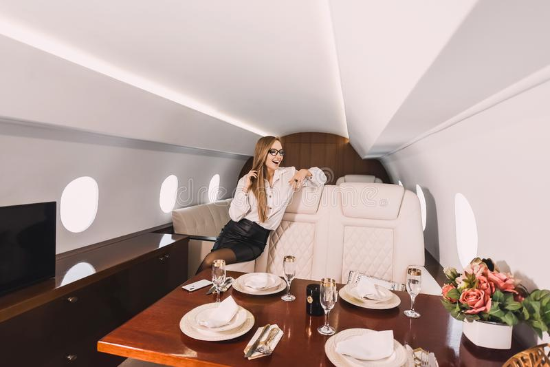 Young girl in the cabin of a business class airplane with a phone in her hands comfortable luxury travel royalty free stock photography