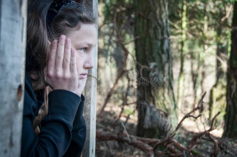 Beautiful young girl, child, in the woods, daydreaming, thoughtful, holding his head in his hands royalty free stock photo